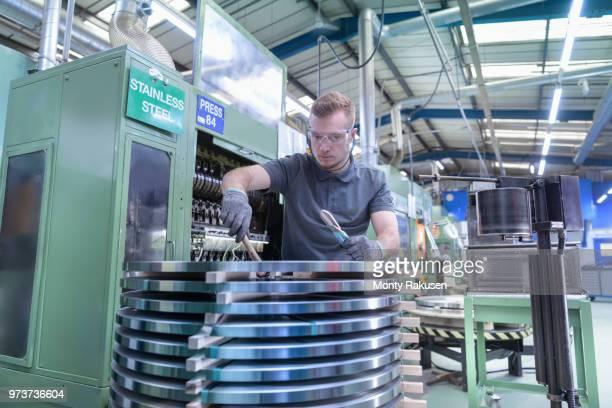 engineer loading steel into pressing machine in metal pressing factory - monty rakusen stock-fotos und bilder