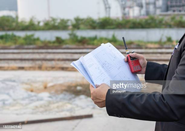 engineer looking at construction drawings and oil refinery industrial plant background. - greenpeace stock pictures, royalty-free photos & images