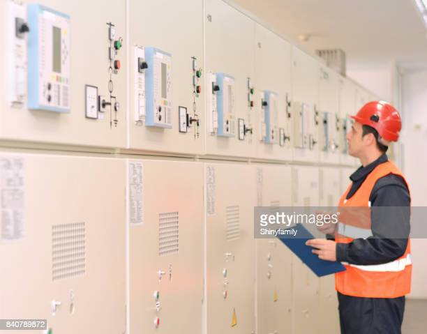 Engineer looking at file in front of control panel