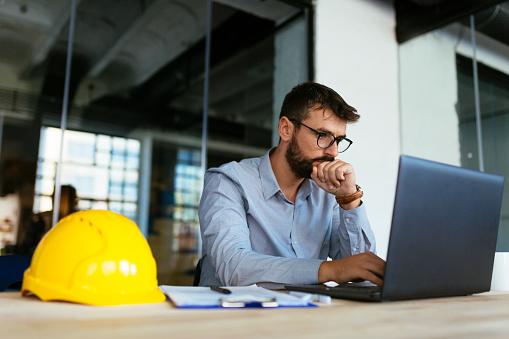 Engineer looking at laptop 1062918366