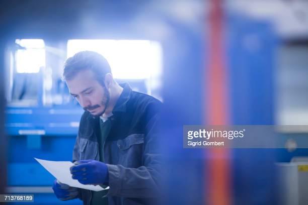 engineer looking at paperwork - sigrid gombert stockfoto's en -beelden