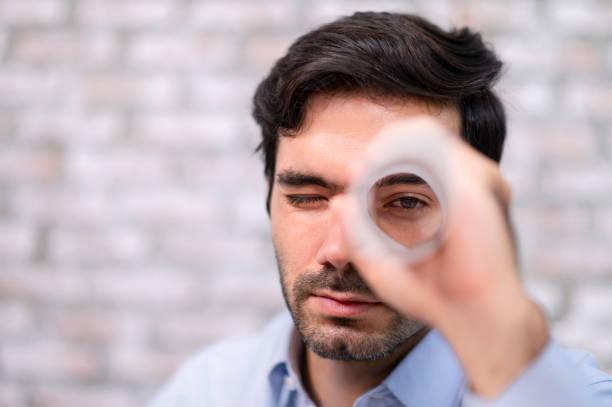 Engineer looking through paper holes