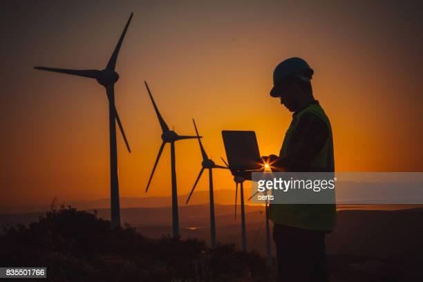 Engineer man using computer in wind turbine farm at sunset