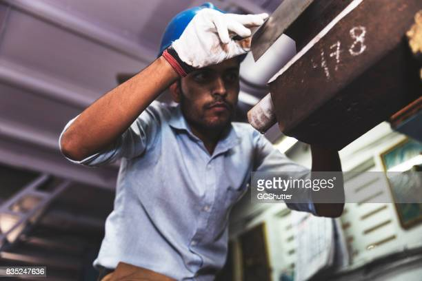 Engineer measuring a sample piece of pipe