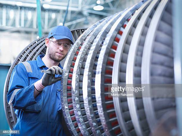 Engineer measuring high pressure steam turbine blade in workshop