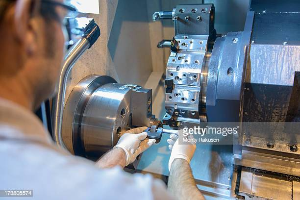 Engineer measuring part on industrial lathe in factory