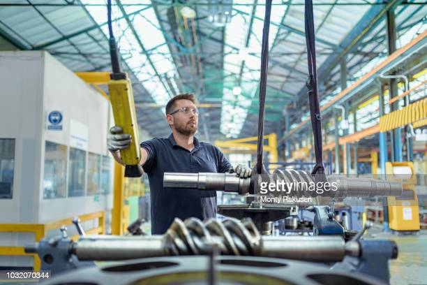 engineer moving partly finished gear parts in gearbox factory - stubble stock pictures, royalty-free photos & images