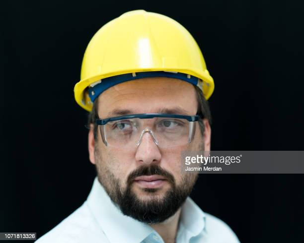 engineer on black background - yellow hat stock pictures, royalty-free photos & images
