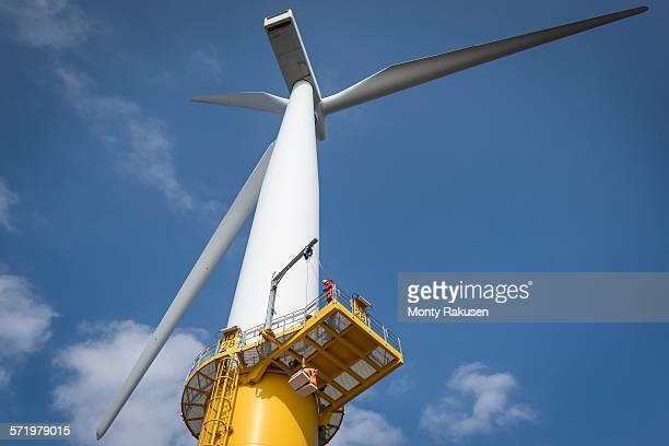 Engineer on wind turbine at offshore windfarm, low angle view