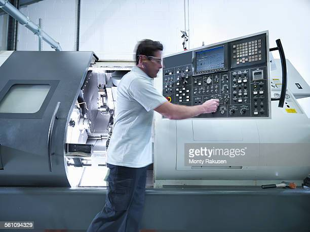 Engineer operating CNC lathe in factory
