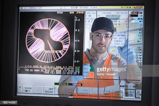 engineer operating cutting machine, view through screen - monty rakusen stock pictures, royalty-free photos & images