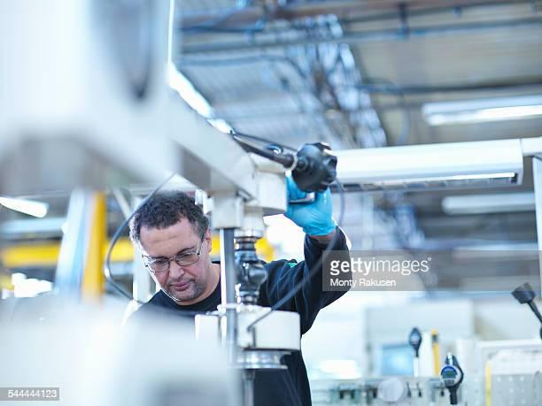 Engineer operating honing machine in factory
