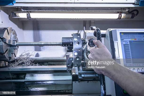 Engineer operating industrial steel lathe