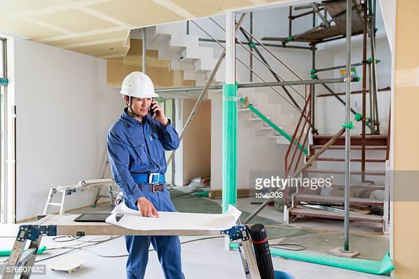 エンジニアまたは検査担当者にビルビュー建設現場スマートフォンで話している