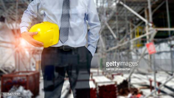 Engineer or Safety officer holding hard hat with blurred construction site background.