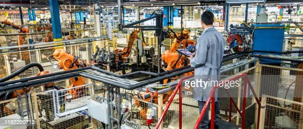 ingenjör övervakar automatiserad produktions process i en fabrik - industri bildbanksfoton och bilder