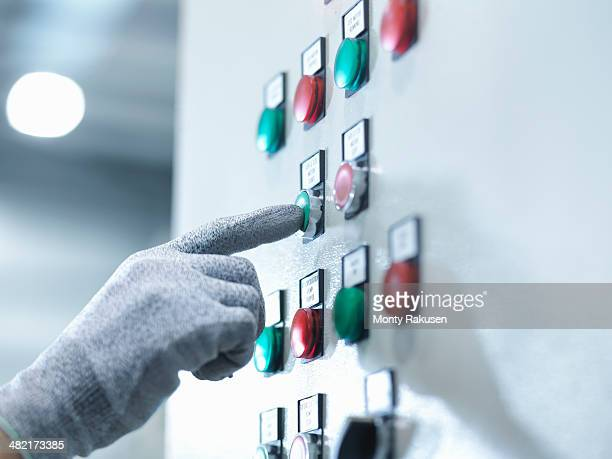 Engineer pressing button in engineering factory, close up