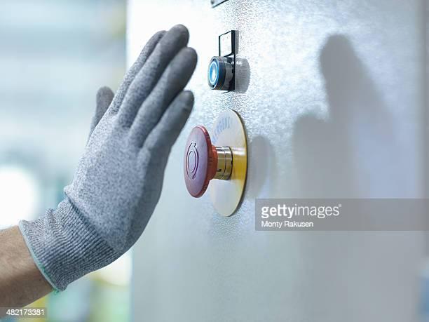 Engineer pressing emergency stop in engineering factory, close up