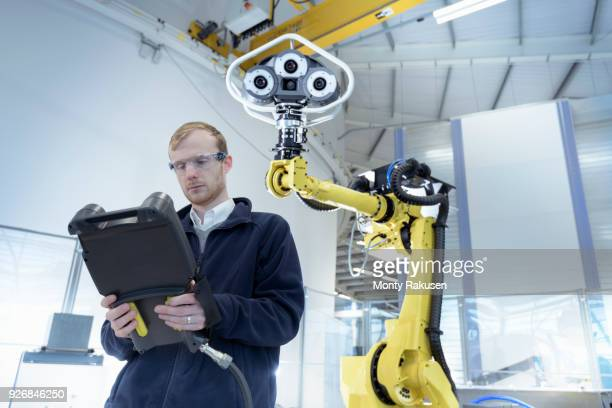Engineer programming robot in robotics research facility