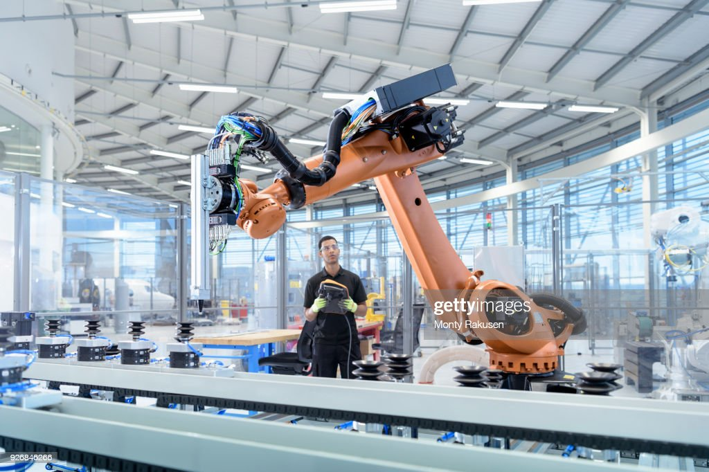 Engineer programming robot in robotics research facility : Stock Photo