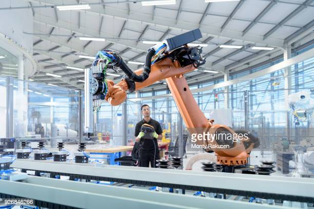 engineer programming robot in robotics research facility - industriebetrieb stock-fotos und bilder