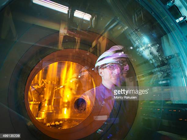 Engineer reflected in glass of fuel rod handling machine in nuclear power station