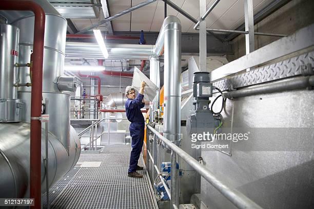 engineer removing cover from equipment in power station - sigrid gombert - fotografias e filmes do acervo