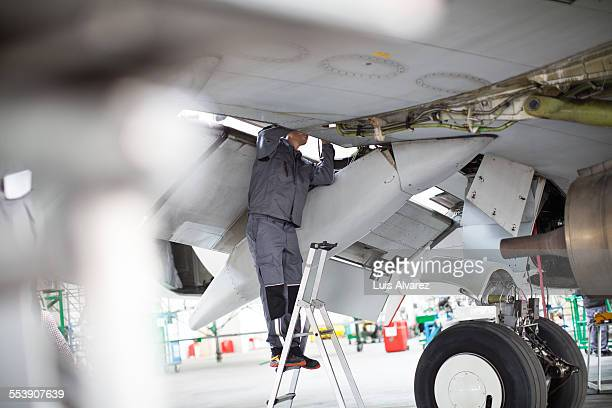 Engineer repairing aircraft on ladder