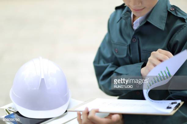 Engineer reviewing  documents outdoors
