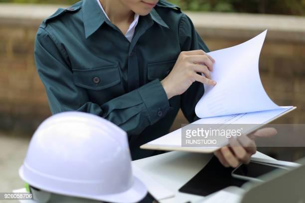 Engineer reviewing paperwork outdoors