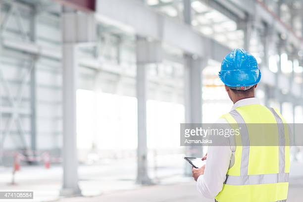 Engineer reviewing plans for construction site on digital tablet