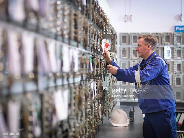 engineer selecting equipment keys in power station - monty rakusen stock photos and pictures