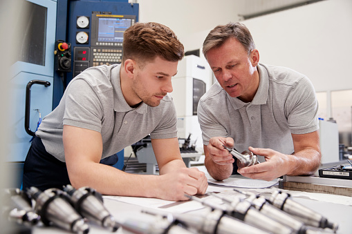 Engineer Showing Apprentice How To Measure CAD Drawings 946236868