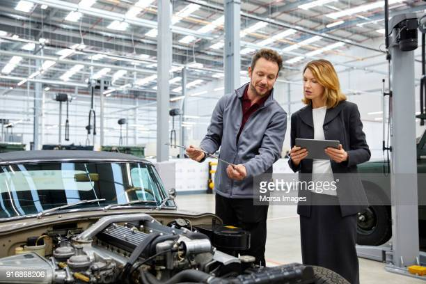 engineer showing dipstick to supervisor by car - automobile industry stock pictures, royalty-free photos & images
