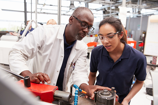 Engineer showing equipment to a female apprentice, close up 862721458