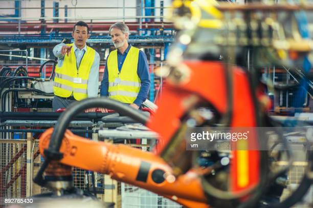 Engineer showing his supervisor the functioning of robotic arms