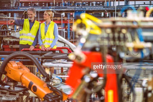 Engineer showing something to young factory manager