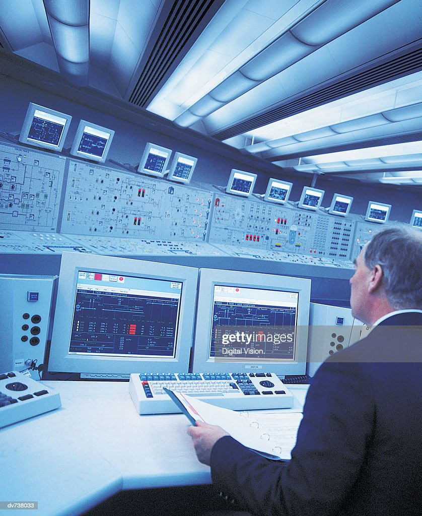 Engineer sitting at control panel of nuclear power station : Stock Photo