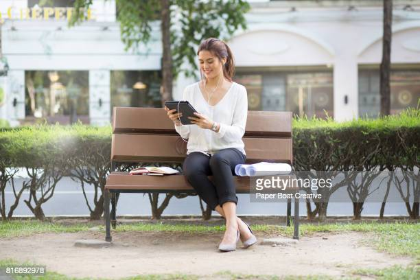 Engineer sitting on a bench at a park outside her office, waiting for her boss for an executive meeting at the coffee shop nearby, while scrolling through her ipad