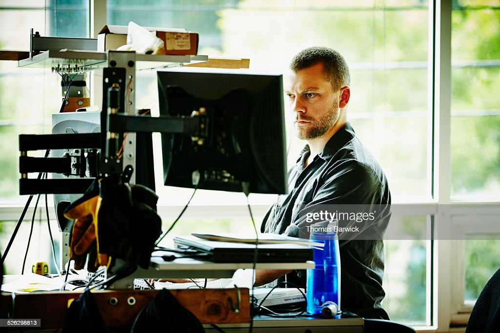 Engineer standing at desk designing project : Stock Photo
