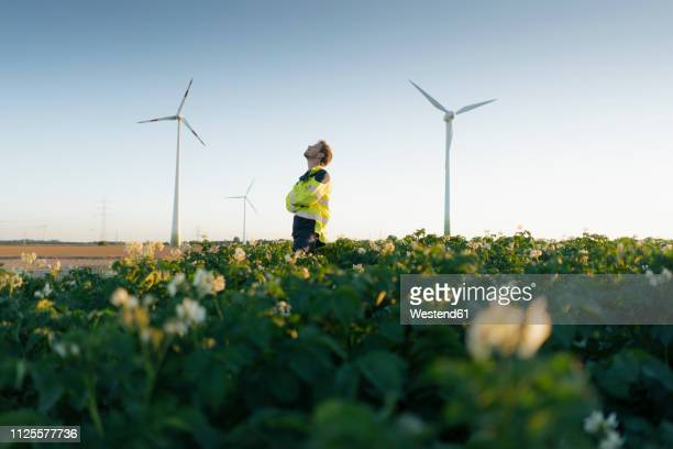 engineer standing in a field at a wind farm - business finance and industry stock-fotos und bilder