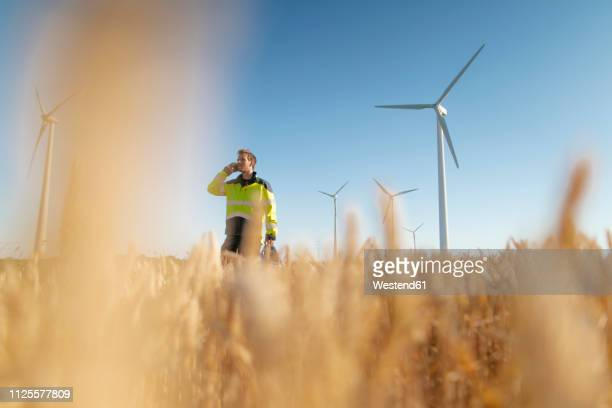 engineer standing in a field at a wind farm talking on cell phone - hearing protection stock pictures, royalty-free photos & images