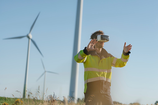 Engineer standing in a field at a wind farm wearing VR glasses - gettyimageskorea