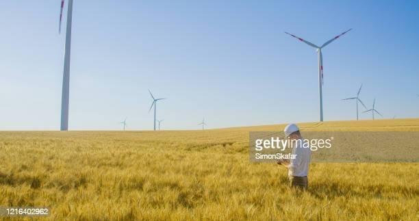風力タービンで小麦畑に立ち、オーストリアの電話を使用するエンジニア - 持続可能エネルギー ストックフォトと画像