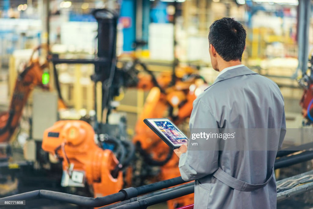 Engineer supervising autonomous producton process : Stock Photo