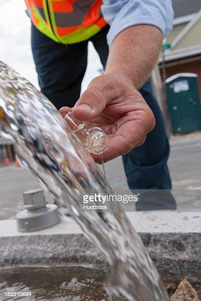 Engineer taking a water sample from a street hydrant
