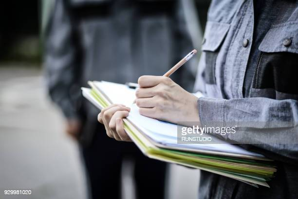 Engineer taking notes with clipboard outdoors