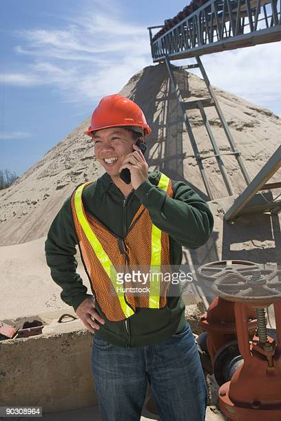 Engineer talking on a mobile phone at control valves