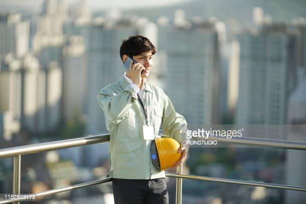 engineer talking on smartphone on rooftop - ヘルメット ストックフォトと画像