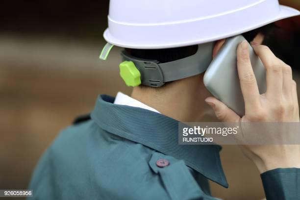 Engineer talking on smartphone outdoors